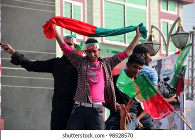SIALKOT, PAKISTAN - MAR 23: PTI Supporter dancing while coming at Jinnah Cricket Stadium during a political rally of cricketer turned politician Imran Khan on March 23, 2012 in Sialkot, Pakistan