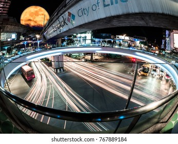Siam, the center of Bangkok, city of light where traffic jams of transportation is there. Here, the giant moon of supermoon phenomenon is also shown behind the sky train in Thailand.
