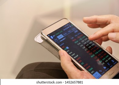 Siam Paragon, Bangkok (15 Jul 19)- Old Asian man is monitoring stock price via mobile app while waiting during family shopping at city shopping mall to keep updated of price movement and situations
