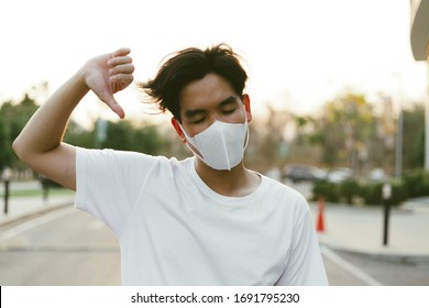 sian thumbs up and wearing protective mask against the corona virus covid 19 brown man wearing surgical mask to prevent from virus white background Corona virus pandemic wearing mask. lockdown city