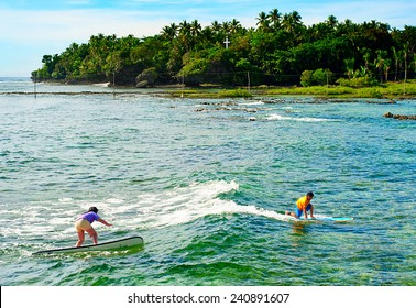 SIARGAO, PHILIPPINES - MAY 11, 2013 :Young people learning to surf at Cloud 9 surfpoint in Siargao, Philippines.  In 2011 3.9 million tourists visiting the country.