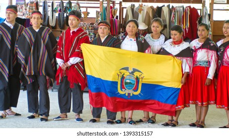 SIBAMBE, ECUADOR - APRIL 12, 2019:  Indigenous dancers holding an Ecuadorian flag at a train station in the Devil's Nose Railroad