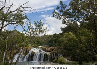 SIBENIK, CROATIA - AUGUST 12 2017: Day view of Krka waterfalls in the natual park, with people bathing in the lake