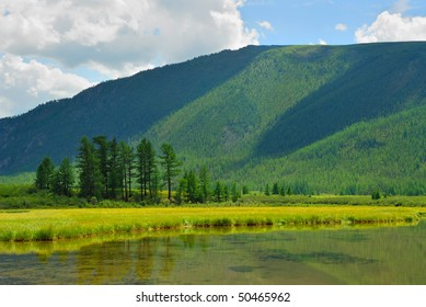Siberia. Altai. View on green valley. Green mountains, blue sky, yellow flowers, calm lake water