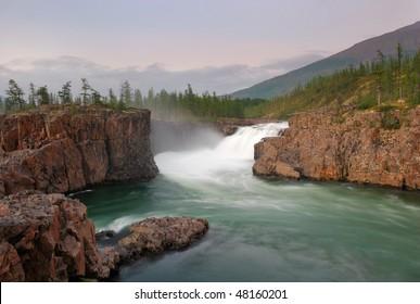 """Siberia. Magic waterfall at Putorana plateau on Dulismar river at a sunset. White stream between orange basalt rocks. Green water and green firs"""