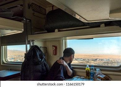 SIBERIA, RUSSIA - MARCH 20, 2018: The Russian passenger is watching outside from train. Khabarovsk, Russia.