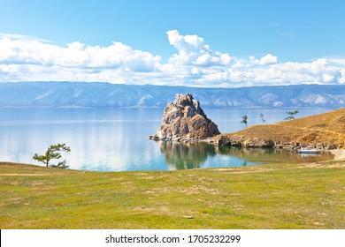 Siberian Baikal Lake in summer sunny day. Rock Shamanka - a natural landmark of Olkhon Island. Beautiful calm landscape. Natural background