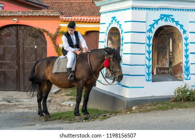 SIBIEL, TRANSYLVANIA/ROMANIA - SEPTEMBER 16 : Young man in traditional dress on a horse in Sibiel Transylvania Romania on September 16, 2018. One unidentified person