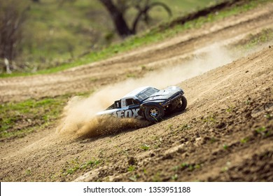Sibiu, Romania - 03.18.2019: TRAXXAS Slash 4x4 Rc car Fox edition on the hills, off-road competition, close up when make drifts and leaving dust behind