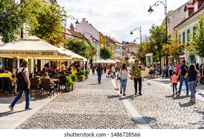 Sibiu, Romania - 2019. People and tourists having lunch and wandering on the streets of Sibiu old town.
