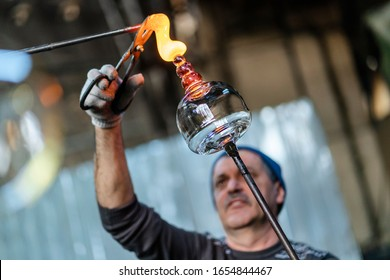 Sibiu, Romania - 21 feb 2020: Close-up shot of glassblower artist working in a glass factory where products are created manually. Detail with the hot molten glass manually poured by the craftsmen.