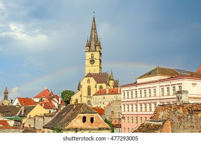 SIBIU, ROMANIA - AUGUST 10, 2016: The Lutheran Cathedral of Saint Mary, most famous Gothic-style church in Transylvania. Colored rainbow on the sky.