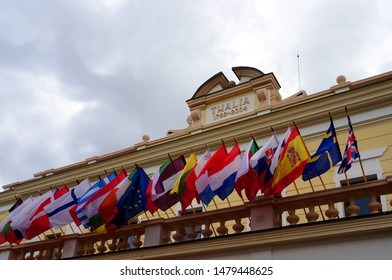 SIBIU, ROMANIA - AUGUST 3, 2019: Flags of EU member states waving on the balcony of the Sibiu State Philharmonics - Thalia Concert Hall. Built between 1787 and 1788 it was Romania's first theatre.