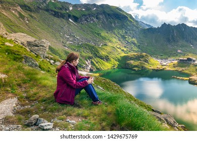 Sibiu, Romania - July 05 2018: Tourist enjoys view of the lake near Transfagarasan mountain road, Romanian Carpathians.