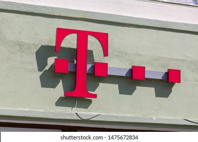 SIBIU, ROMANIA - June 27, 2019: T Logo above the entrance of a Deusche Telekom Shop. Mobile, Dax, communications, T-Mobile, magenta, brand, sign, internet, phone, business, carrier, network, store.