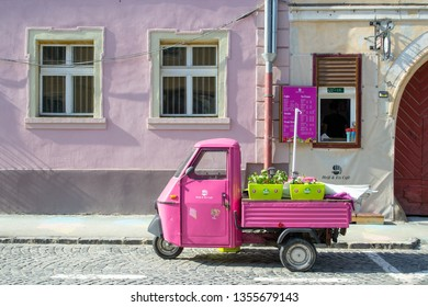 Sibiu, Romania - March 25, 2019: Heiss and Eis Cafe front window with an old pink tuk tuk parked in front, menu displayed on a purple table, and two big windows, on a hot Summer holiday.