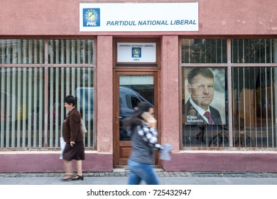 SIBIU, ROMANIA SEPTEMBER 22, 2017: People walking in from of the local office of PNL Party (Partidul National Liberal, National Liberal Party), with a picture of Prime Minister Klaus Iohannis in front