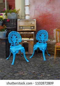 Sibiu, Sibiu/Romania - 12/10/2015: Blue chairs, flower pots and old radios at a café on a street in Sibiu
