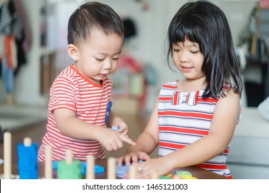 Sibling Big sister and baby brother playing with lots of wooden toys block at home.Kids play with educational toys at home.Day care and Kindergarten school.child development concept.