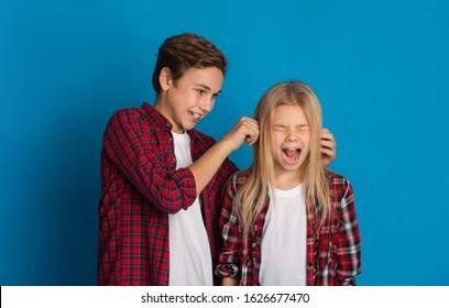 Sibling relationship concept. Elder brother teasing little sister, pulling her ears till she scream, standing together over blue studio background