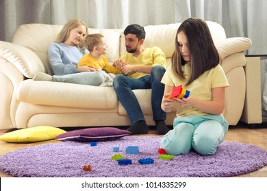 sibling relationship. Parents play with a younger child. The eldest child hurt. Jealousy in the family. Children's jealousy, resentment.