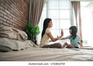 兄弟姉妹が家でベッドで一緒に遊ぶ