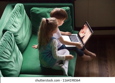 Siblings boy and girl enjoying kid cartoons on youtube using laptop together sitting on sofa at home, preschool children sister and brother focused on watching interesting video online spending time