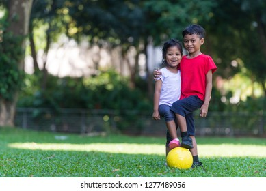 Siblings - boy and girl - playing football at a park. South east asian, Muslim children. Cute and happy expression