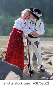 Siblings, brother spontaneously kissing smiling sister. Children wearing traditional Polish mountain people clothes standing on rocks at stream. Vertical crop