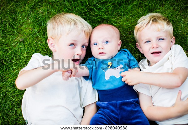 Siblings brothers bonding with newborn baby