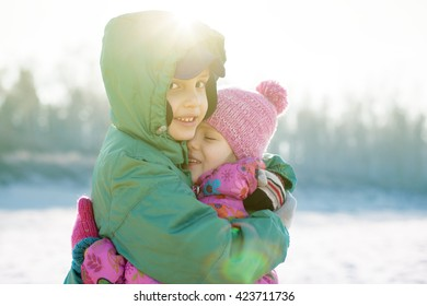 siblings children happy hug backlight playing outside selective focus stylized
