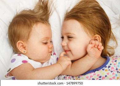 Siblings cuddling in bed