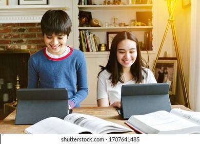Geschwister machen ihre Schularbeit von zu Hause aus während der sozialen Distanzierung - Homeschool - Happy - Tablets
