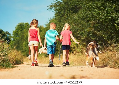 Siblings with dog in nature. Two girls and one boy holding toys and going to play.