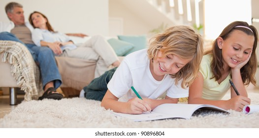 Siblings doing their homework on the carpet with their parents behind them