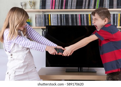 Siblings fighting over the remote control in the living room in front of the TV