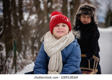 siblings having fun in the snow on the sledge