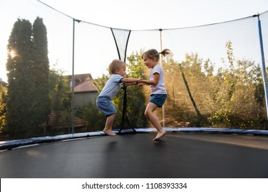 Siblings having fun as they jump on trampoline