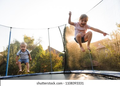Siblings having fun together outside on trampoline