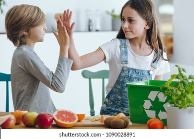Siblings high fiving while segregating biodegradable waste in the kitchen