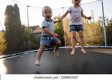 Siblings jump on trampoline while holding hands