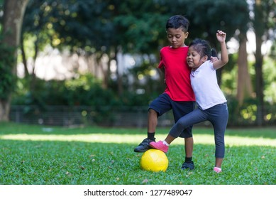 Siblings - Malay boy and girl - pose with football at a park. South east asian, Muslim children. Sports for the young concept. Happy expression