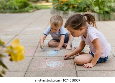 Siblings playing in backyard - children drawing with chalk on paving