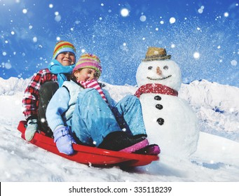 Siblings Playing Snow Sledge In The Snow Concept