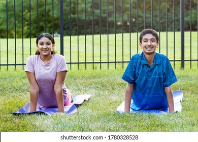 Siblings Practicing Yoga Outdoors in the Morning