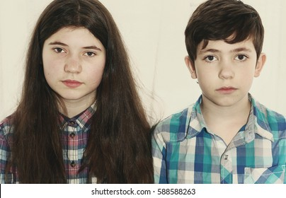 siblings preteen boy and teenager girl with long thick brown hair brother and sister close up portrait isolated on white