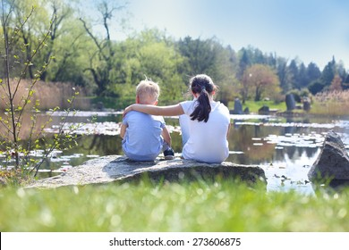 Siblings, sister, brother hugs . Two children, older sister and younger brother sitting on the shore of the lake