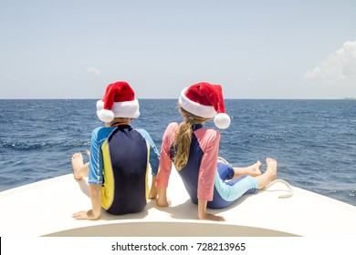 Siblings sit on the front of a boat in the Caribbean and enjoy the sun at Christmas time.