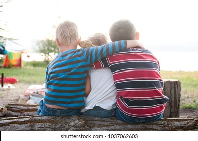 Siblings Sitting On Log With Arms Around Each Other