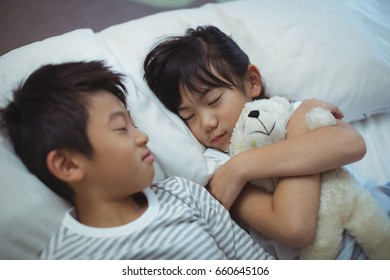 Siblings sleeping on bed in bed the room at home